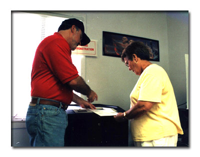Marty shows a voter how to fill out her ballot.